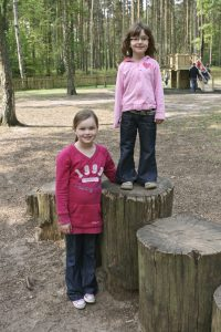 Beth and Emily standing near the tree stumps on the adventure playground at the Sandringham Estate in Norfolk.