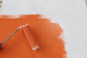 Painting the plywood orange using a mini-roller