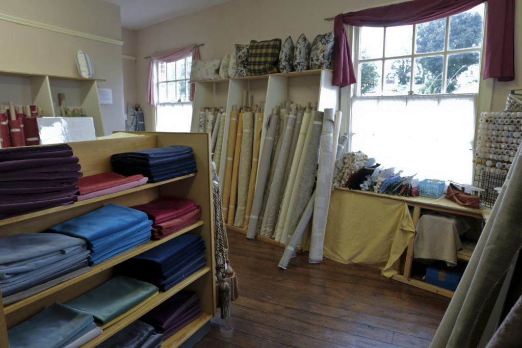 Upstairs in Bargain Fabrics, Castle Donington. Fabric on rolls, haberdashery & large pieces of fabric in piles on shelves.