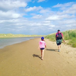Emily and Richard walking along the beach from Holkham to Wells