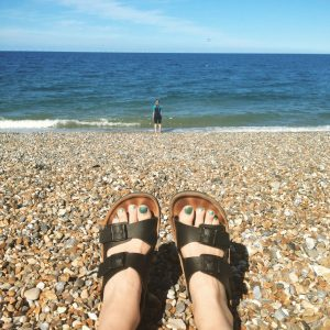 My feet in Birkenstocks with the pebble beach and see in the background.