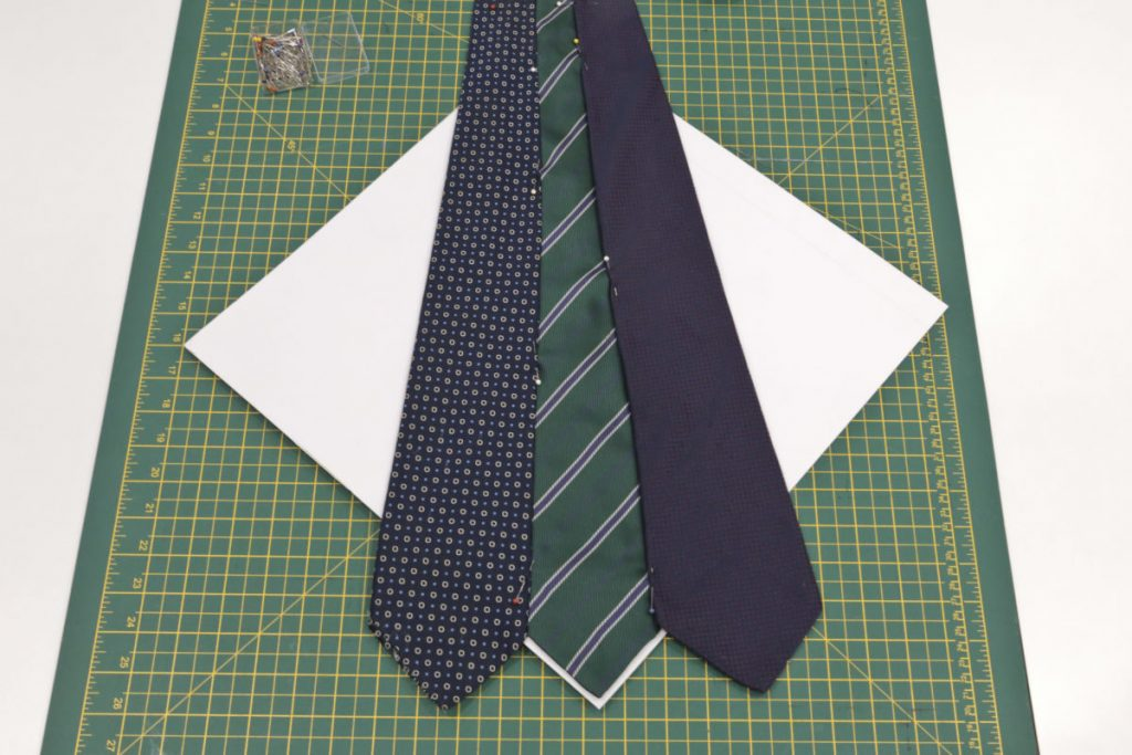 Three ties are laid on the white cardboard square cushion template.
