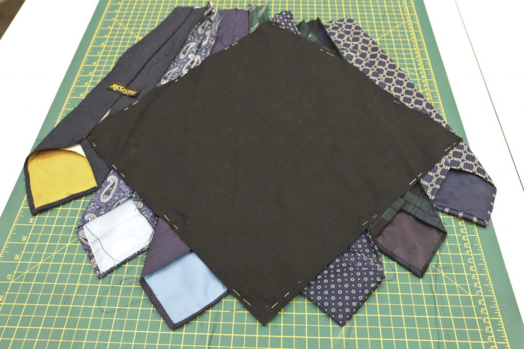 The black square of lining fabric is fixed to the wrong side of the ties that have been sewn together prior to sewing in pplace and the excess fabric being cut away