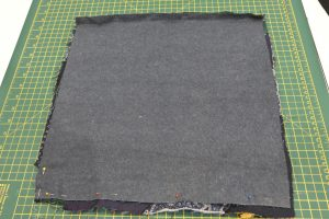 Picture of the entire square cushion tacked in place with zip pinned in place prior to sewing