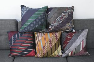 5 different colour schemes of cushions made from neck ties stacked on a sofa.