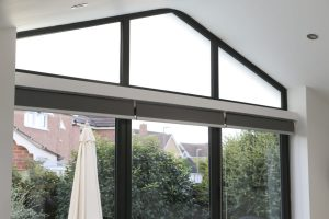 Awkward shaped triangular windows above the folding doors with the frosted glass static window film applied