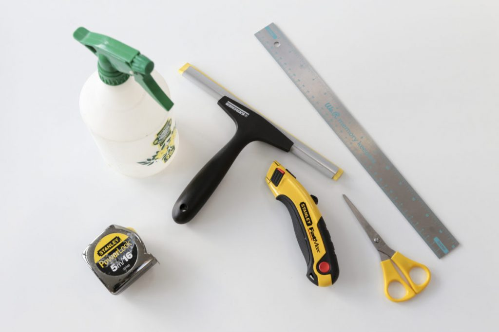 All of the tools you need to add window film to your windows. Rubber squeegee, ruler, stanley knife, scissors, spray bottle filled with water, tape measure