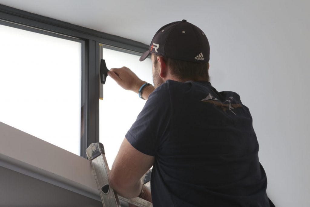 Mr T using a squeegee to apply the frosted glass window film to our awkward shaped windows above our folding doors.