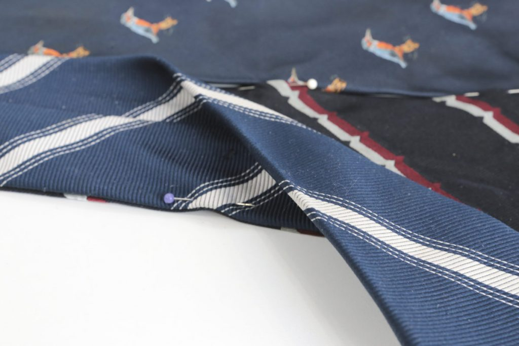 The pins that held the ties together are repositioned so the two ties are placed together right side facing and their edge aligned. Pin them in place and then sew them together along their length, 2-3mm in form the edge.