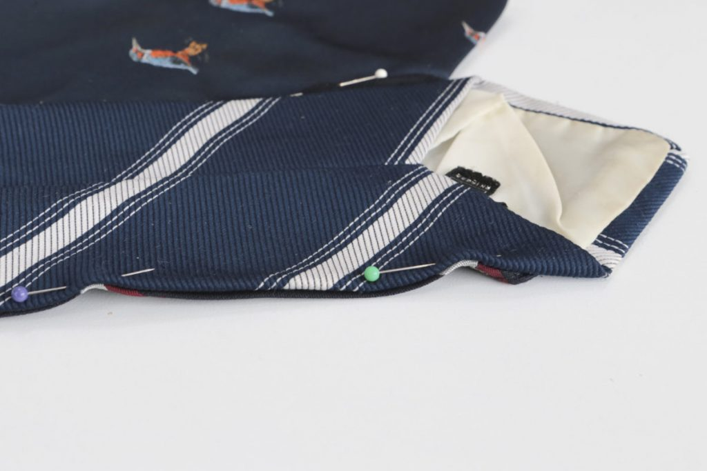 Close up of the two ties pinned to each other prior to sewing. The pins that held the ties together are repositioned so the two ties are placed together right side facing and their edge aligned. Pin them in place and then sew them together along their length, 2-3mm in form the edge.