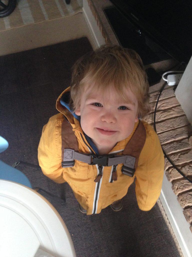 My nephew in his yellow raincoat and dinosaur backpack