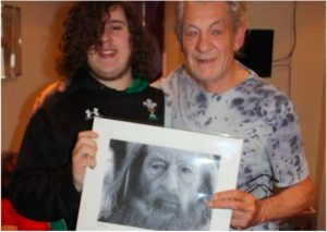 Chris Baker presenting one of his heroes, Ian McKellen, with his drawing of Gandalf.
