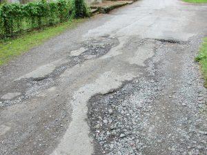 damaged road with potholes