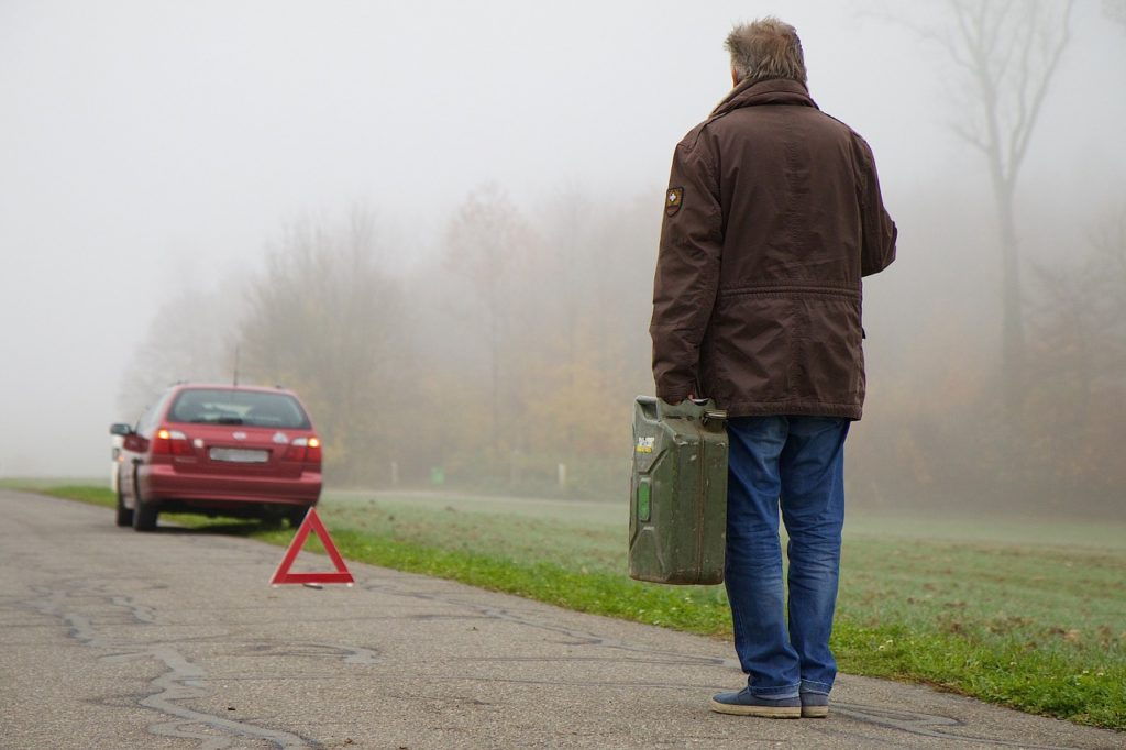 Man walking towards broken down car with petrol can