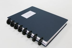 A side view of my Blue Arc customisable notebook. You can see the plastic disks that form the spine of the notebook.