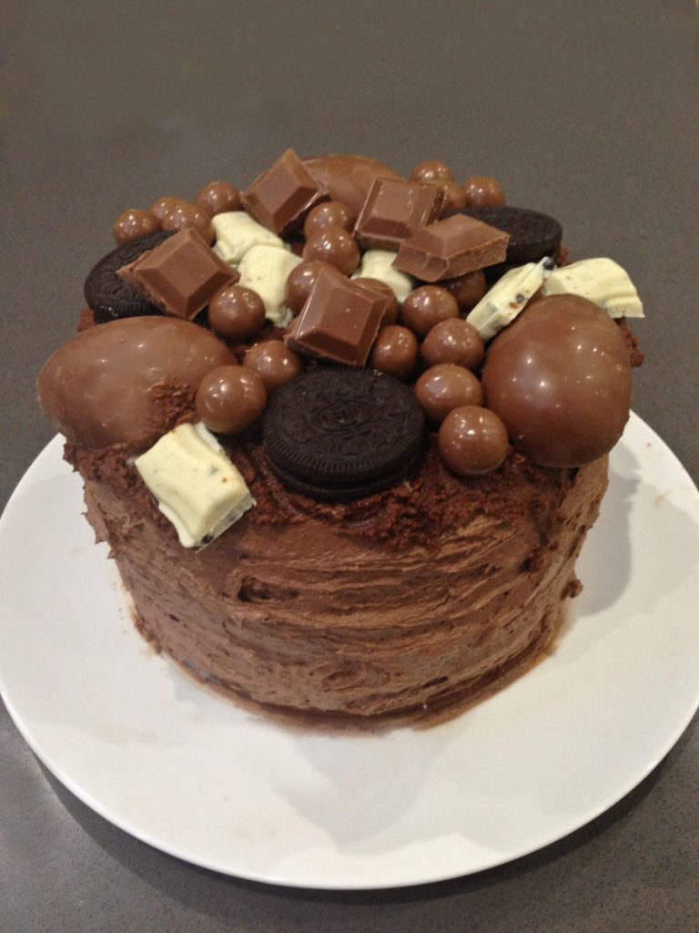 Beth's Chocolate Cake of Dreams. A victoria sponge cake covered in Maltesers, Oreos, White Chocolate, Milk Chocolate and Kinder Surprises