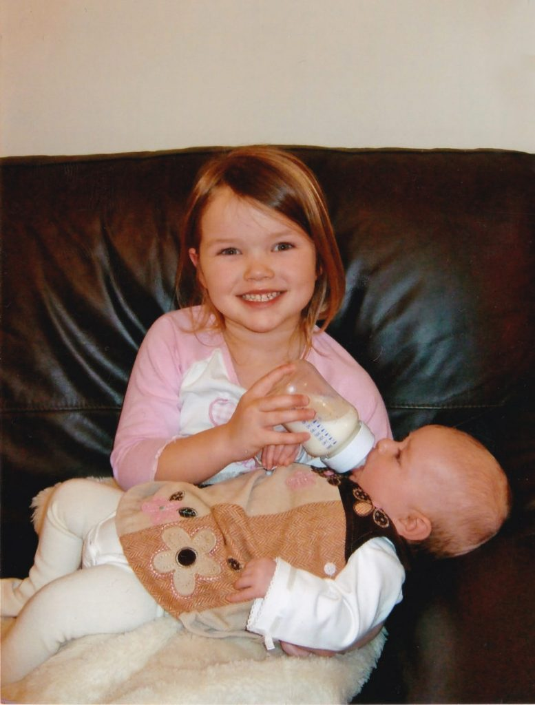 Beth feeding her little sister, Emily.