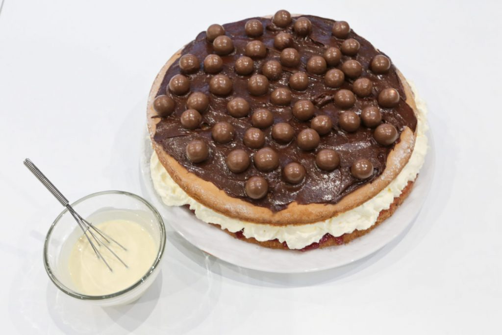 Melt white chocolate and drizzle it over the Malteser covered cake
