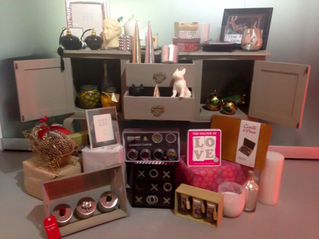 Christmas gifts on top of and in the drawers of a sideboard