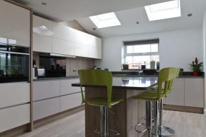 View towards kitchen window, with tiled porcelain floor, kitchen island unit