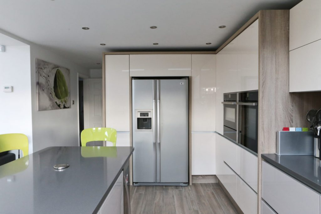 View of kitchen showing american style fridge, gloss cream units