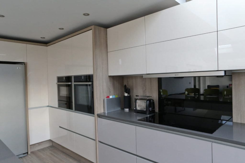 Gloss cashmere and jasmine cream kitchen units, handleless design in modern kitchen with oak laminate splashback