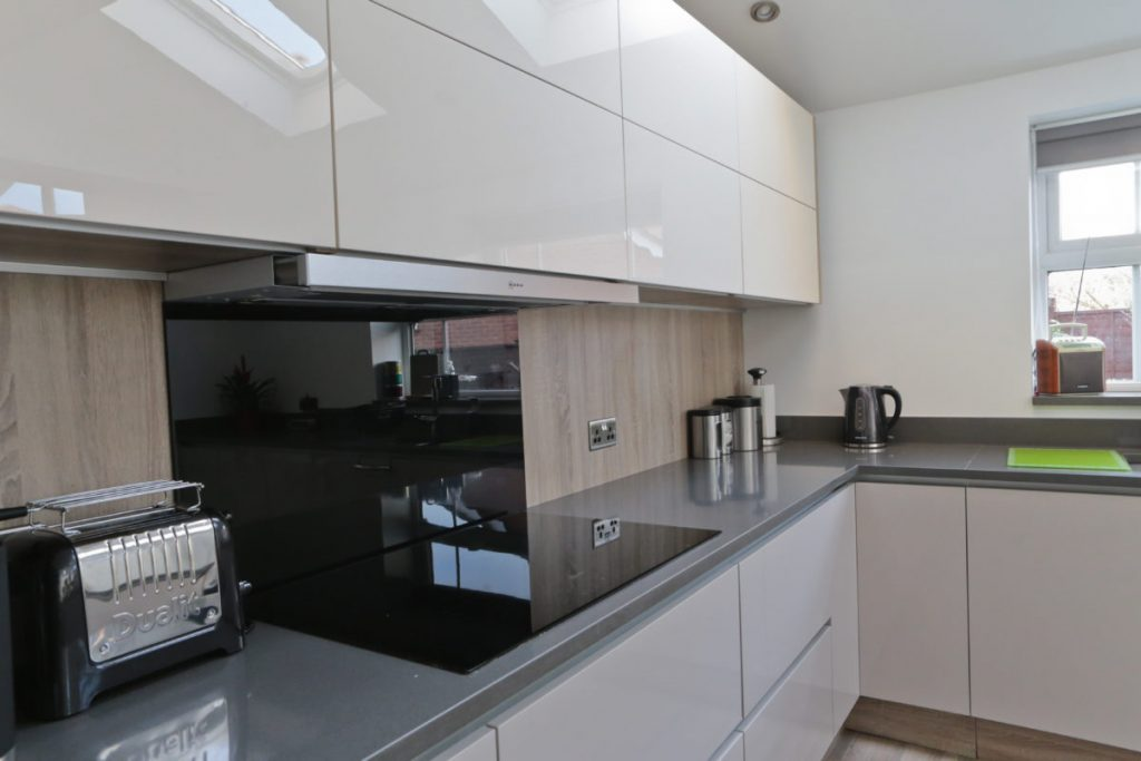 Gloss modern kitchen with induction hob built into grey quartz granite worktop