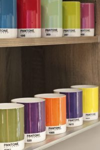 Wood interior to kitchen cupboard with Pantone mugs on shelves