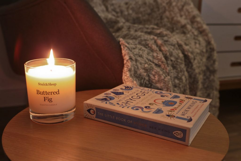 Close-up of candle alight on a side table with the Little Book of Hygge beside it