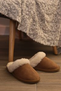 Hygge means sheepskin slippers, seen here near a chair with a cable knit throw on it