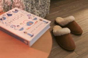 Soak & Sleep Sheepskin Slippers on the floor and Hygge book in the foreground