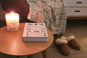 Candle and Hygge book on side table near an armchair with cable knit throw and slippers on floor