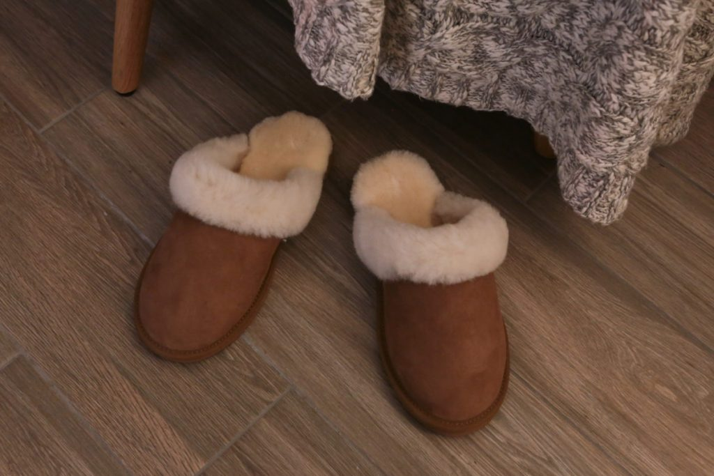 Close-up of sheepskin slippers on wood effect tile floor with cable knit throw in background