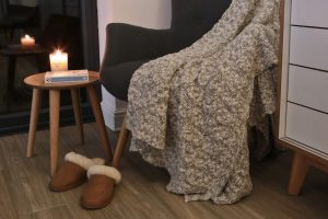 Ultimate Hygge with a cosy corner chair, slippers, candle, book and throw
