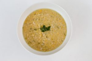Chunky Chicken & Sweetcorn Soup in a white bowl on a white table with a sprig of parsley on top.