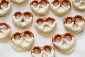 The white chocolate coated pretzels are left to cool on a plate covered with greaseproof paper