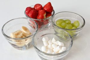 Bowls of ingredients for the santa hat skewers: strawberries, grapes, bananas, marshmallows