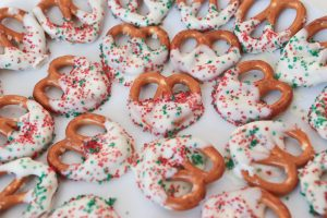 Pretzels coated in white chocolate with green and red sugary sprinkles on top