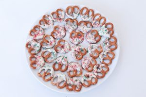 Pretzels coated in white chocolate with green and red sugary sprinkles on top arranged on a white plate