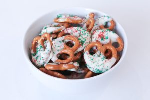 A bowl of pretzels coated in white chocolate with green and red sugary sprinkles on top