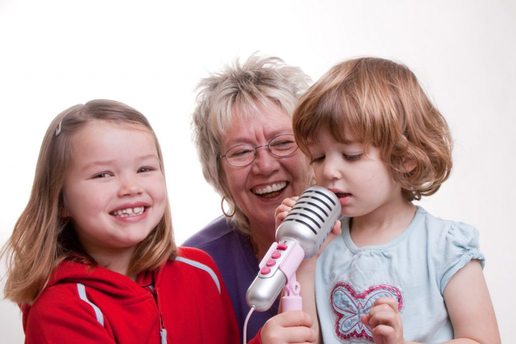 Grandma, ELdest and Youngest with youngest singing into a mic
