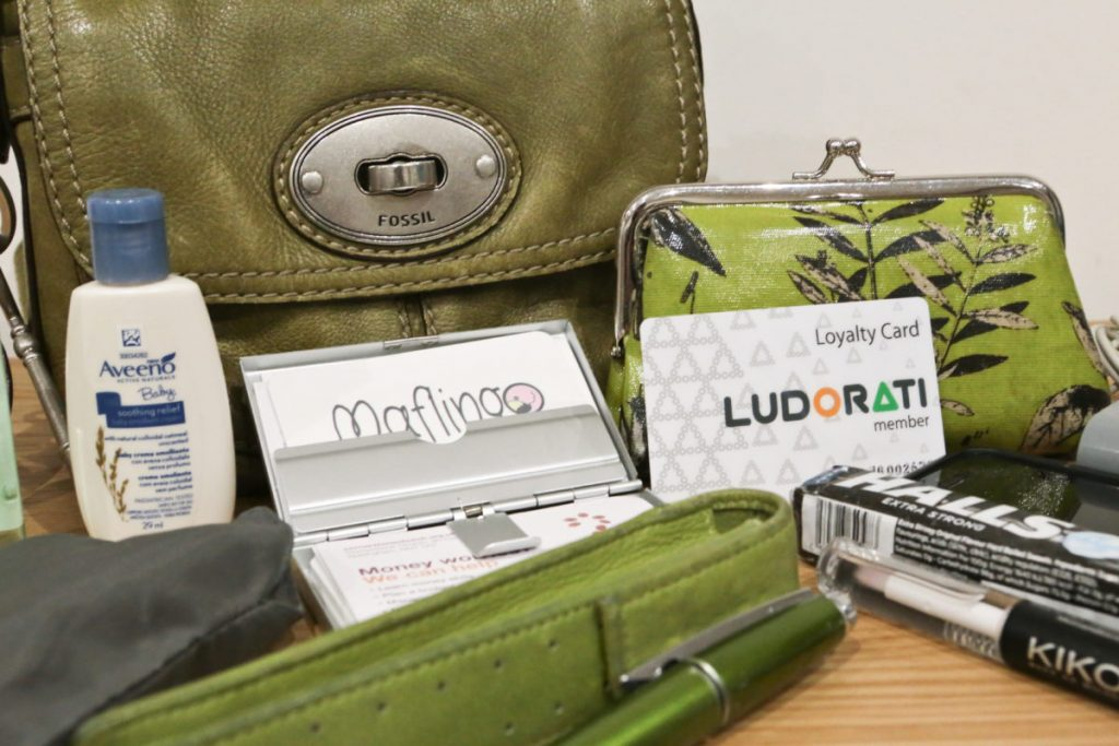 Close-up of my green Fossil handbag with Cross Edge pen and case, Green floral clasp purse, Moo business cards, Ludorati loyalty card, Halls cough sweets, Aveeno cream, Carrier bag