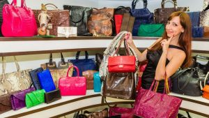 Lady in front of shelves filled with handbags