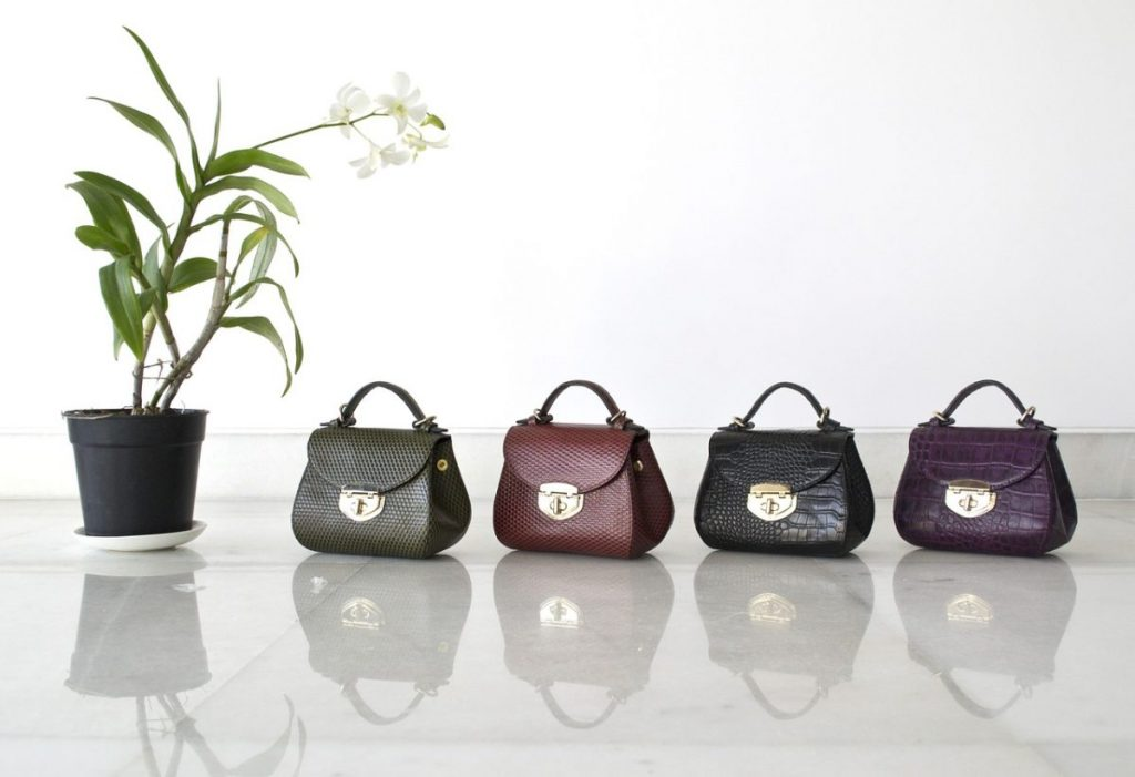 Four different coloured leather handbags in a row