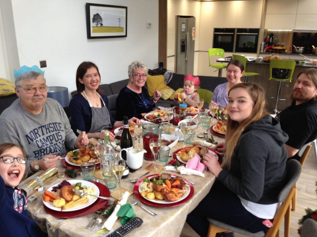 All of the family gathered around the Dining Table eating Christmas Dinner