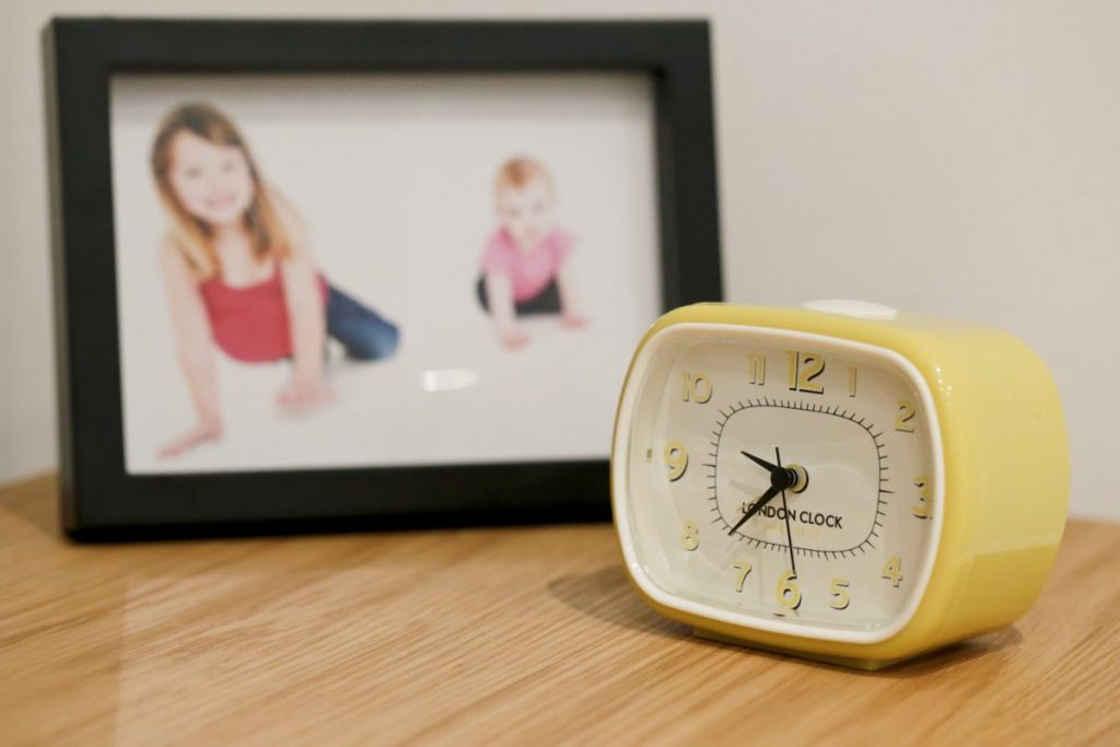 London Clock Yellow Retro Alarm Clock on a table with a photo of our girls in the background