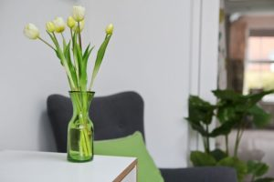 Wayfair Pantone Greenery inspiration close-up of tulips in a green vase with grey chair and cushion in background