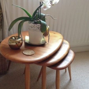 My mum's ercol pebble table nest in light wood with plant and gold ornaments on,
