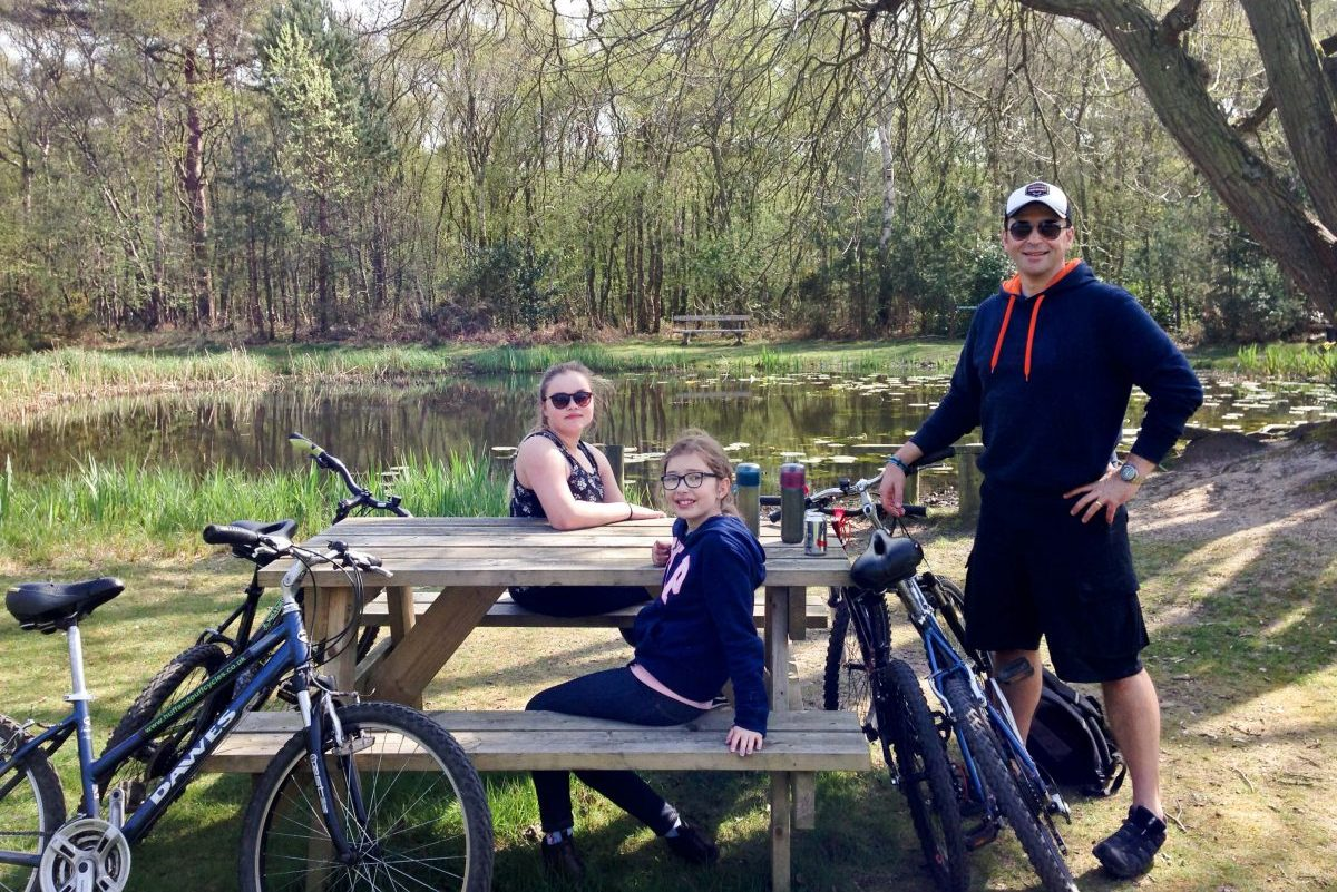 Sitting at picnic bench beside pond on Kelling Heath Holiday Park Cycle route
