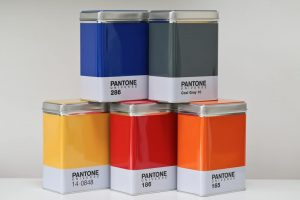5 Stacked Pantone Universe kitchen storage containers / tins in different colouts against a white background